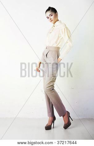 Pretty Stylish Girl In White Trousers And Blouse Posing