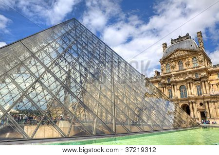PARIS - JUNE 06: Glass Pyramid and Louvre (former Royal Palace) on background on June 06, 2012 in Paris, France. The Pyramid is one of the main touristic sites and serves as entrance to Louvre museum.
