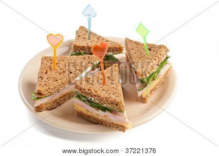 Grupo de sanduíches de chá com queijo, presunto e alface em um prato isolado no fundo branco