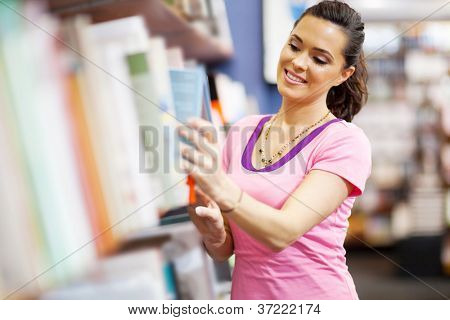 young woman choosing a book in bookstore