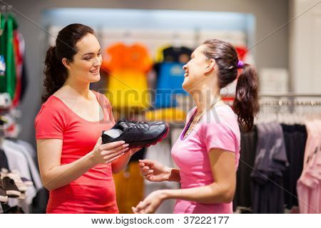 shop assistant helping customer choosing sports shoes