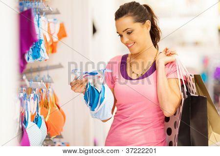 mulher jovem atraente comprar roupa em loja de roupas