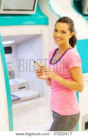 happy young woman withdrawing cash at an ATM