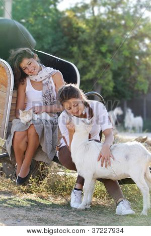 two young happy women with cat and goat on farm outdoor portrait
