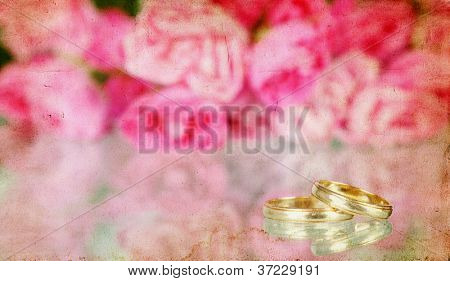 Pink roses and wedding rings on vintage background