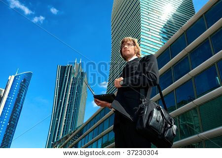 Young businessman standing with laptop in the big city and purposefully looking away.