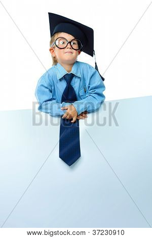 Portrait of a cute little boy in academic hat and big spectacles holding white board. Isolated over white background.