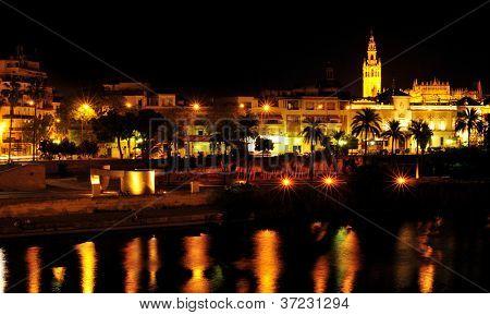vista de Sevilla, en la noche con el río Guadalquivir en primer plano y la Giralda en la backg