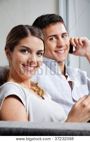 Portrait of beautiful young woman smiling with man on phone call