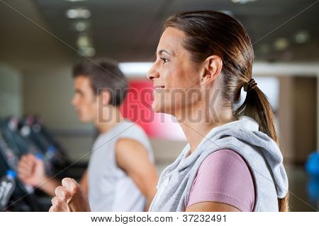 Side view of mature woman and man running on treadmill in health club