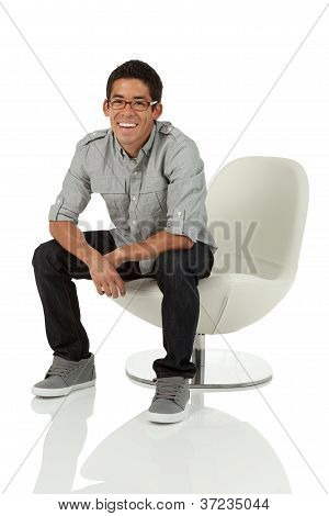 College age man sitting on a modern chair