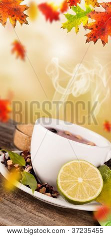 Autumn cup of tea with concept of falling leaves