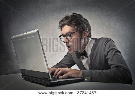 Fashionable boy surprises while using a laptop computer