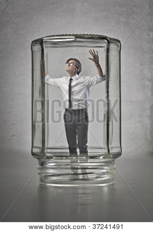 Businessman trapped in glass container