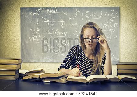 Beautiful blonde girl studying at school