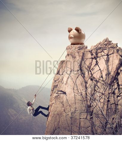 Young businessman scaling a rock to reach a large piggy