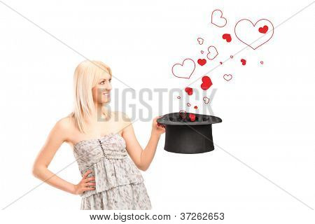 A smiling blond female holding a top hat and hearts around isolated on white background