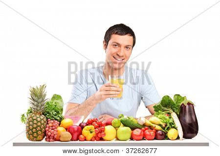 Handsome guy with glass of orange juice, on a table full of fruits and vegetables isolated on white background