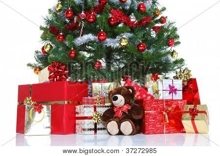 Decorated Christmas tree with baubles and tinsel surrounded by gift wrapped presents and a teddy bear, isolated on a white background. The teddy is generic, not a brand name bear