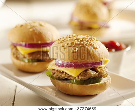 close up of mini burgers with cheese, onion and pickle.