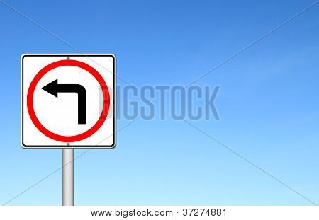 Left Turn Road Sign Over Blue Sky
