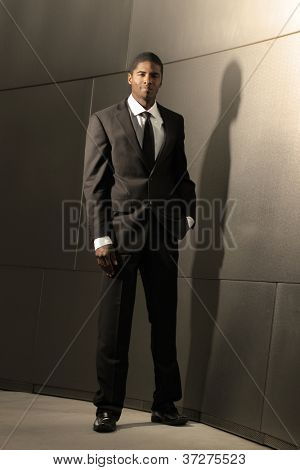 Striking portrait of a young good looking successful businessman in suit leaning against modern shiny building