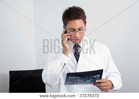 Young male dentist looking at X-ray report while using cellphone in clinic