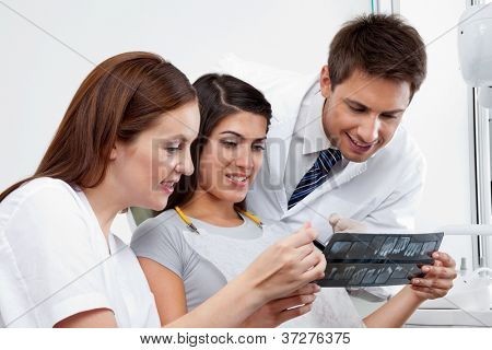 Female nurse and dentist explaining X-ray report to patient with doctor in the background
