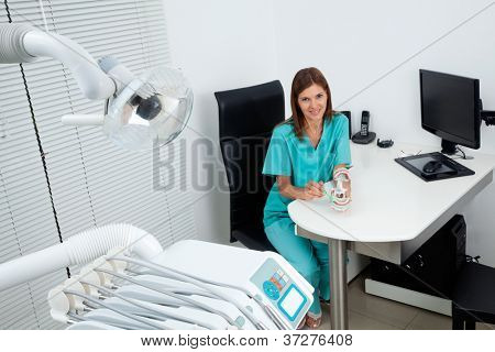 Portrait of happy female dentist explains how to brush your teeth at desk