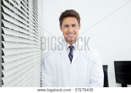 Portrait of happy young male dentist standing in clinic