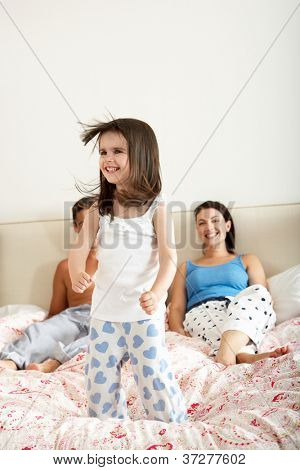 Family Bouncing On Bed Together