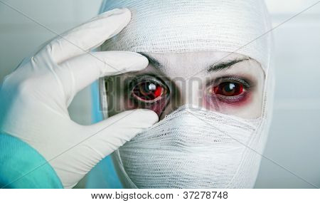 Evil doctor checking results of genetic experiment, opening eye of bandaged patient