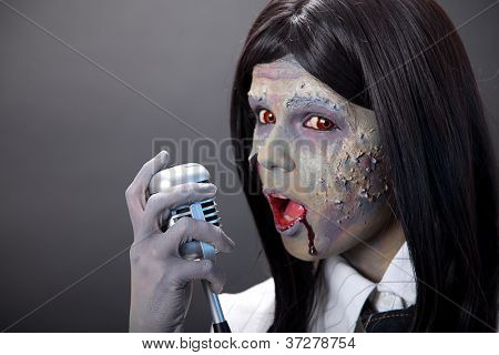 Cute zombie girl singer with retro microphone, studio shot