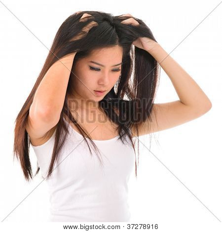 Young Asian girl scratches her hair on white background