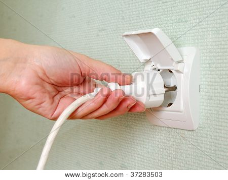 Sticking Electric Plug In Socket On Wall