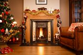 stock photo of quaint  - Decorated fireplace in a family home with Christmas tree - JPG