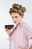 Portrait of beautiful young female with hair curlers holding giant glass of wine