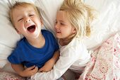 stock photo of tickle  - Brother And Sister Relaxing Together In Bed - JPG