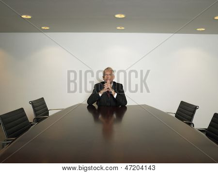 Portrait of thoughtful businessman with hands clasped sitting alone in conference room
