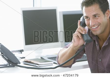 Handsome businessman using landline phone at office desk