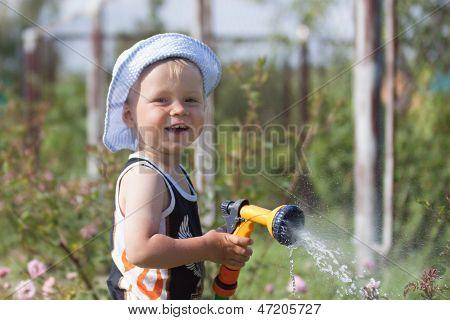 Smiling little boy spraying a hose