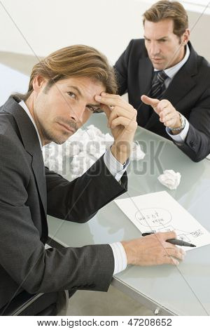 Portrait of frustrated businessman with manager shouting at him in office