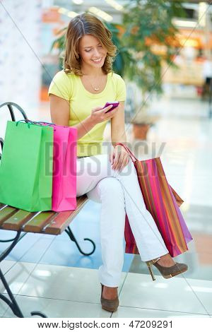 Vertical portrait of a charming girl sitting on a bench in a shopping gallery and reading sms