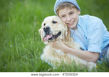 Portrait of cute lad embracing his fluffy friend while lying on grass