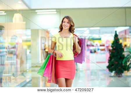 Young woman admiring shop-window in the mall