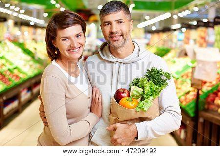 Imagem de casal feliz com paperbag cheio de produtos olhando para câmera no supermercado