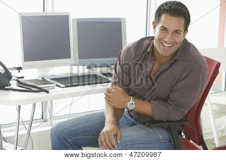 Portrait of smiling businessman in casualwear sitting by computer desk in office
