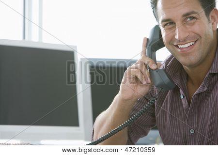 Smiling businessman using landline phone in office