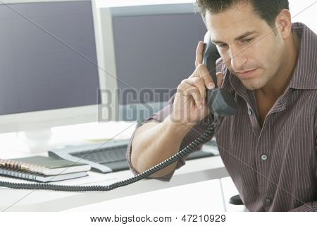 Serious businessman using landline phone at office desk