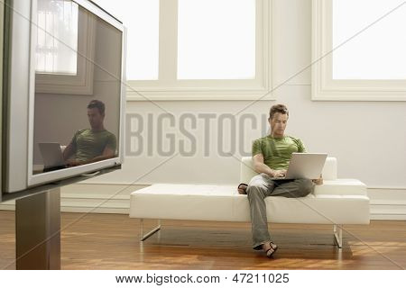 Full length of young man using laptop on sofa in modern apartment